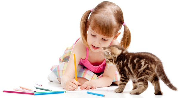 A young girl coloring while her brown kitten watches